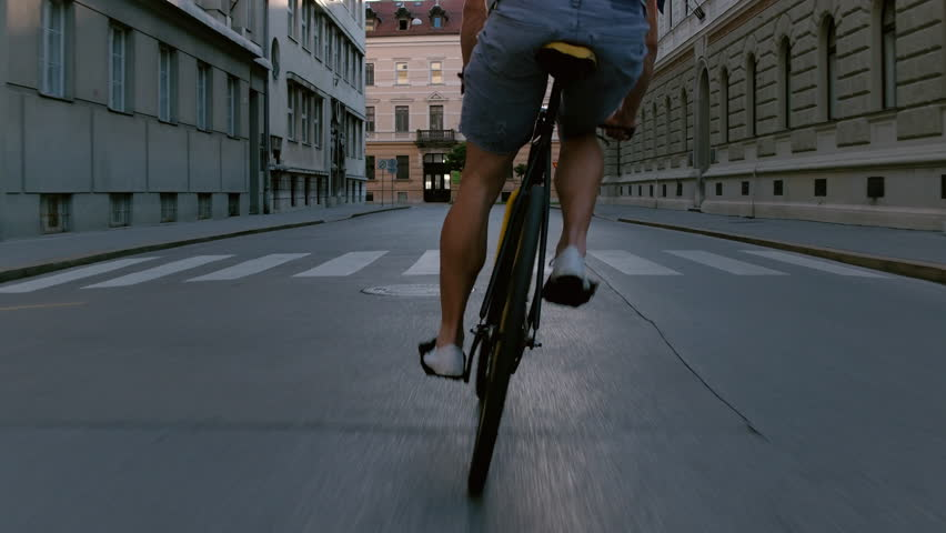 Behind young man swerving with his bicycle in the middle of the city street | Shutterstock HD Video #20913781