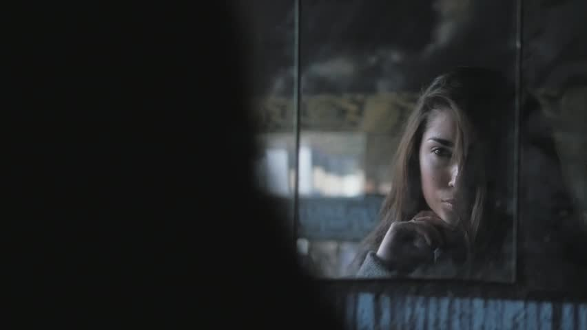 Beautiful young brunette girl with long hair looking at herself in a broken mirrors on street