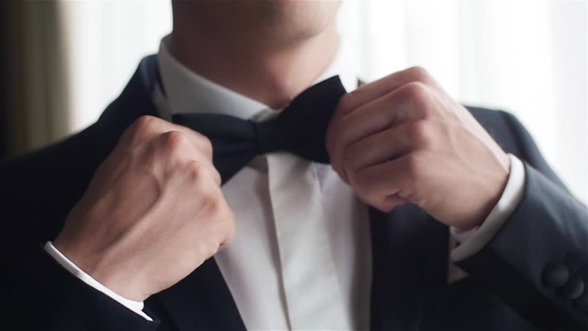Man straightens bow-tie close up slow motion. Well-dressed young man puts and adjusts classic black bowtie on white shirt no face only torso. Success style confidence establishment luxury life concept | Shutterstock HD Video #20943025