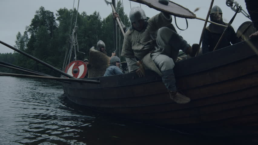 WOLIN, POLAND - 06.08.2016: Viking Warriors Jump off the Row Ship after Arriving to Shore. Slavs and Vikings Festival. Medieval Reenactment. Shot on RED Cinema Camera in 4K (UHD).