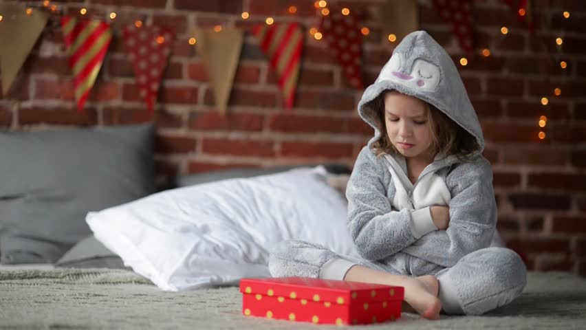 Cute little girl is unhappy with her Christmas gift by a fireplace in a her bed on Xmas morning | Shutterstock HD Video #20970280