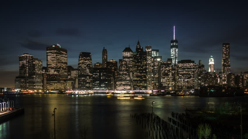 View of Manhattan skyline from Brooklyn waterfront. From day to night. Skyscrapers lights turning on while the night is coming. Time lapse.