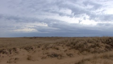 South view of sand dunes, grasslands and clouds from Provincetown beach near race point light house with slight zoom in