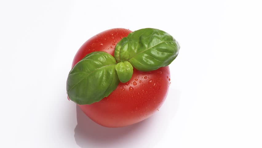A rotating tomato with basil leaves | Shutterstock HD Video #2101757