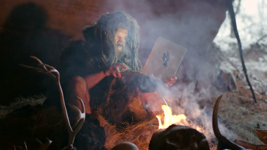 Prehistoric caveman using laptop