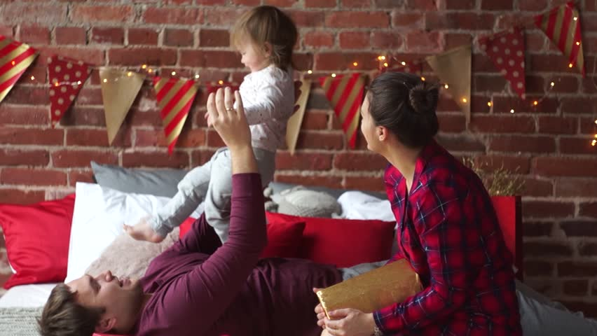 Christmas morning. Young family gleefully congratulates each other Marry Christmas. Young man cheerfully plays with small daughter. Room is festively decorated. Merry Christmas and a Happy New Year. | Shutterstock HD Video #21040261