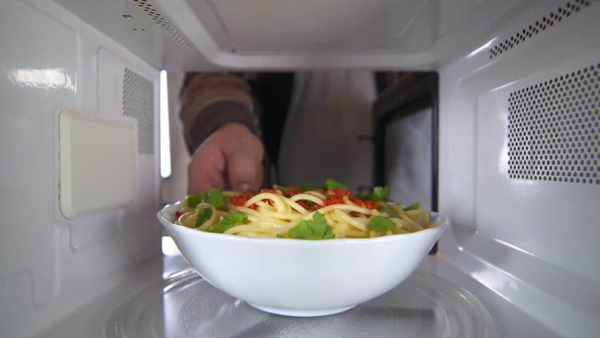 Man wearing a robe heating up cooked pasta dish with tomato sauce in the microwave oven at residential kitchen view inside the microwave
