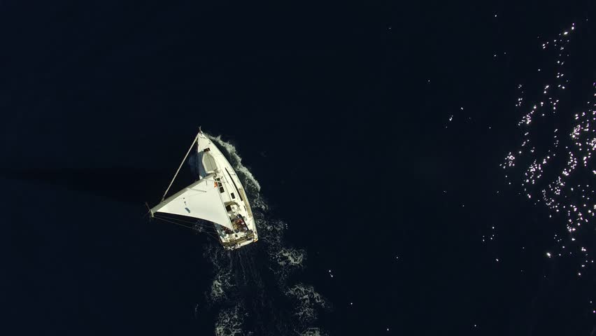 Flying over white yacht in the ocean. Sailing vessel in the sea. The camera is pointing straight down. Aerial view.
