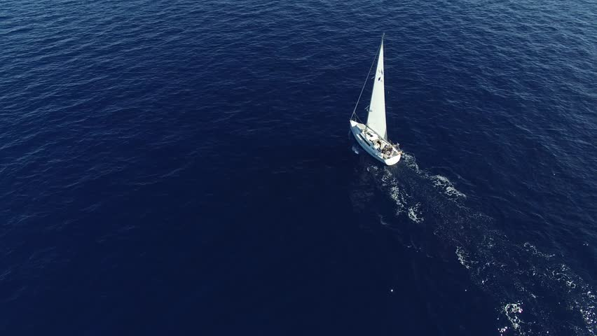 Flying over white sailboat in the ocean. Sailing vessel in the sea. The camera is pointing straight down. Aerial view.