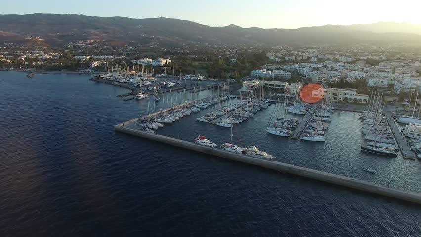 Flying over yacht marina in Kos island. Many boats moored in the marina Aerial view.