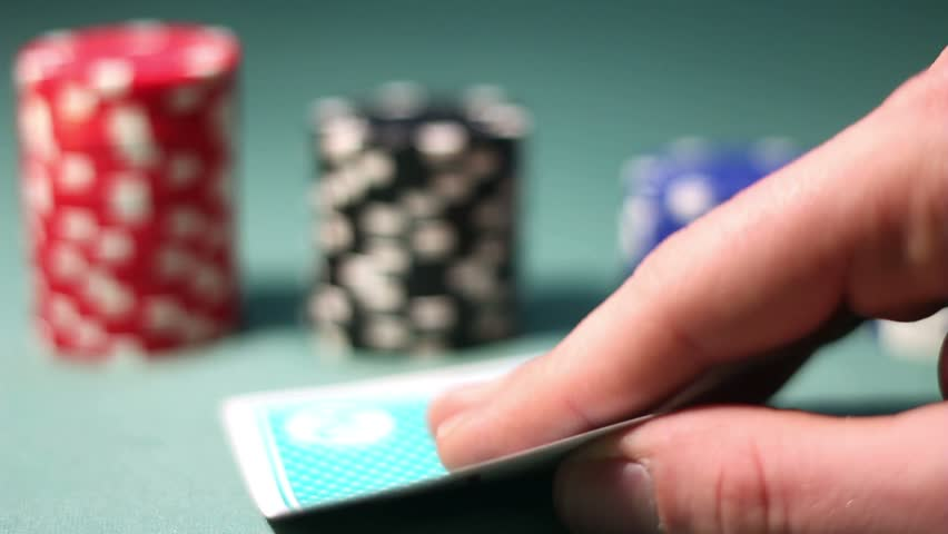 Poker player looks his hand carefully | Shutterstock HD Video #2105747