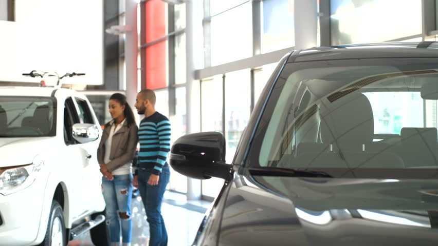 Examining the Wide Range. Beautiful Couple Walking in the Car Dealership Salon Looking at the Cars Choosing a Vehicle to Buy