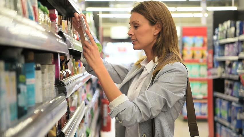 Woman customer scanning hygiene products in grocery store