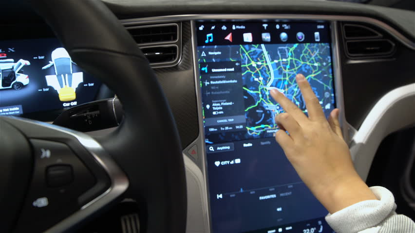 HELSINKI, FINLAND - NOVEMBER 04, 2016: The interior of a Tesla Model X electric car with large touch screen dashboard. Woman tasting a new vehicle functions. DIGIEXPO 2016 in Messukeskus Expocenter.