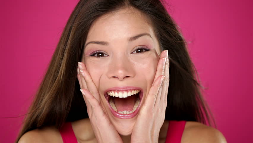 Surprised excited happy woman closeup portrait of beautiful young woman with ecstatic face expressions. Winning young mixed race Asian / Caucasian female model on pink background.