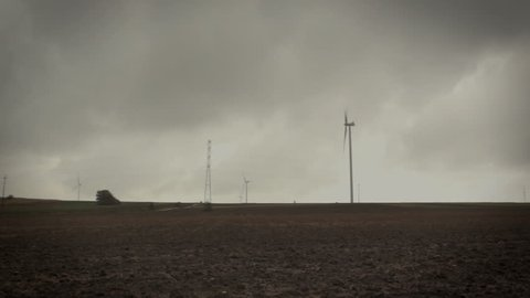 Camera slide over landscape with wind turbines and plowed soil on the empty field at the end of autumn