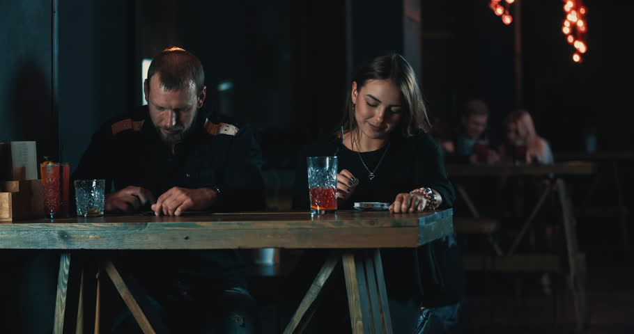 Couple in bar using mobile phone 4k video. Young woman and man touching smartphone. Digital device addiction: internet and social networks concept | Shutterstock HD Video #21180082