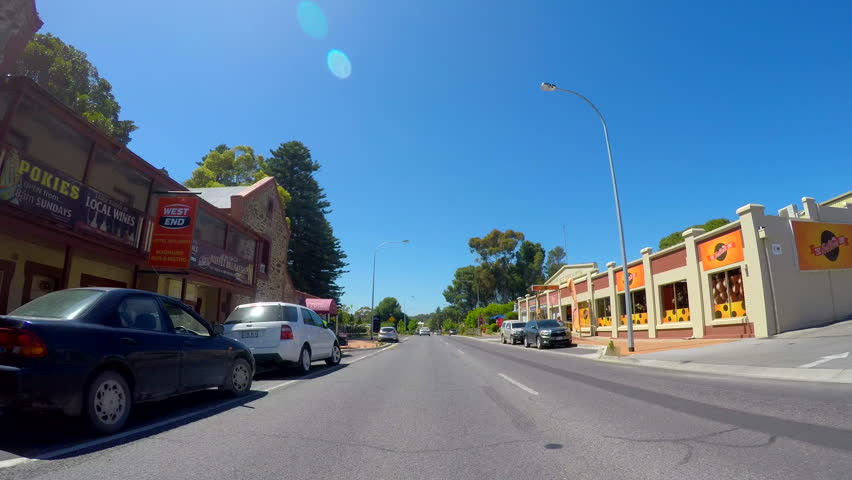 MCLAREN VALE, SOUTH AUSTRALIA - NOVEMBER 5, 2016: Automobile POV driving through the main township of McLaren Vale along Main Road, sunny with lens flare, real time.