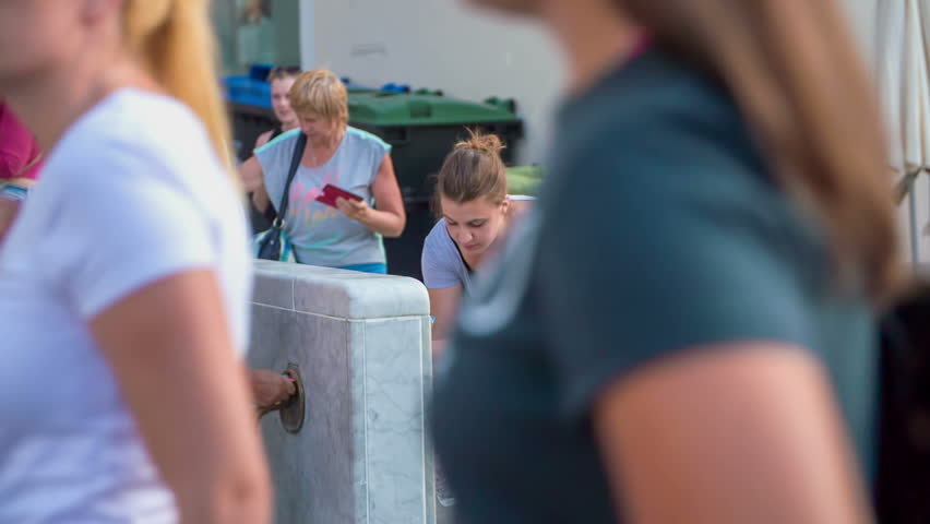 EVENTS IN LJUBLJANA JULIJ-AVGUST 2016 People are washing their hands or filling up their bottles with water. They have come to the Open Kitchen food market. It is summer time. #21193915