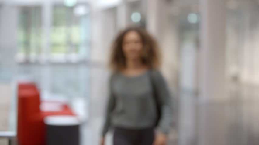 Smiling female university student walking into focus indoors