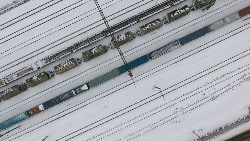 Long freight train coming on the railroad station in winter. Aerial shoot.