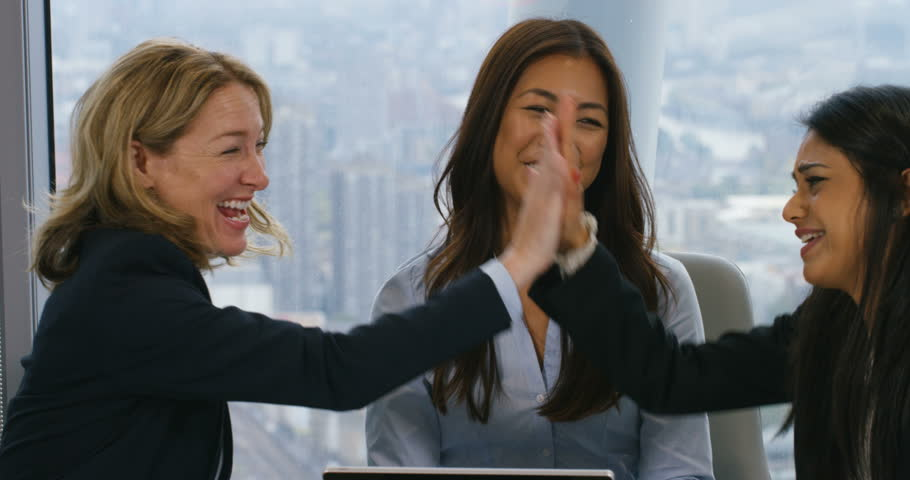 4k, Successful businesswomen giving high-five around a desk during a boardroom meeting.