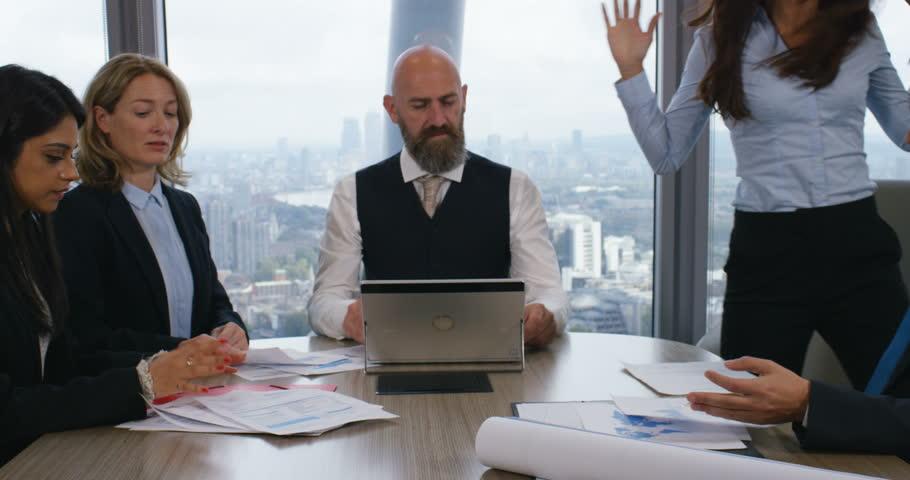 4k, A team of suit-clad businesspeople having a boardroom meeting together in heated debate.
