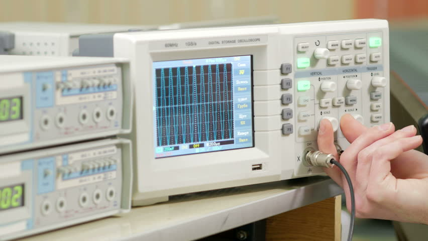 Men's engineering arm adjusts the oscilloscope for proper display of the electrical signal. Modern small industrial oscilloscope