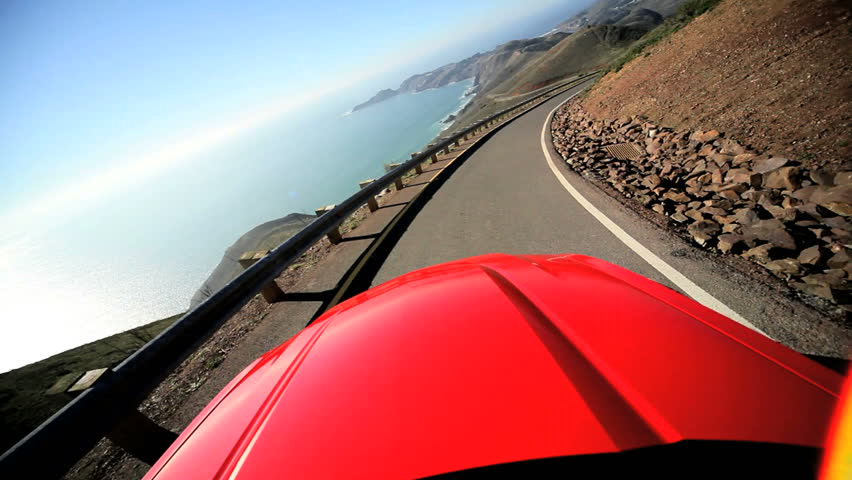 Californian road trip driving a Cabriolet on a winding Pacific highway