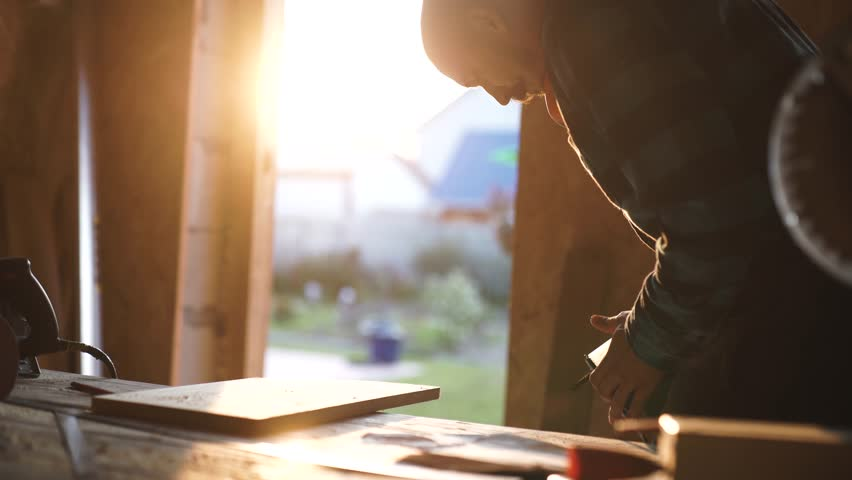 Young bold carpenter with moustache. circular saw cutting piece of wood. sun flare on background
