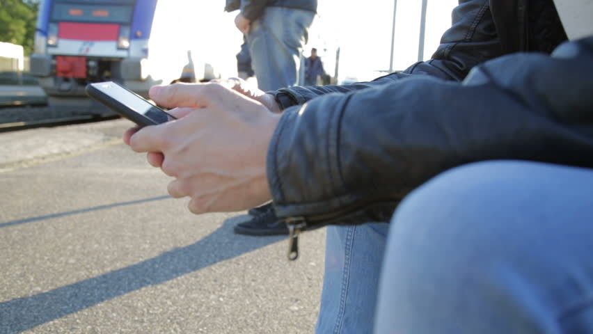 Young man people is using the Smartphone seated in the Train station. | Shutterstock HD Video #21276115
