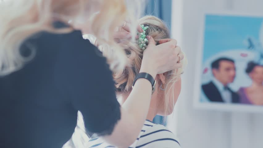 Wedding styling. Wedding hairstyle. Final touches to the hairstyle. Accessory for wedding hairstyles. Decoration in hair. Blonde woman helps the bride to choose the barrette in her hair. | Shutterstock HD Video #21337072