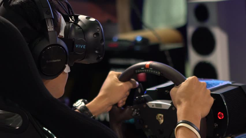 Taipei, Taiwan-28 October, 2016: Slow motion Young Asian Man Wearing Goggles and Playing Video Games of Racing Car with ride simulator. Using Virtual Reality Glasses In 360 Virtual Reality Game -Dan  #21342175