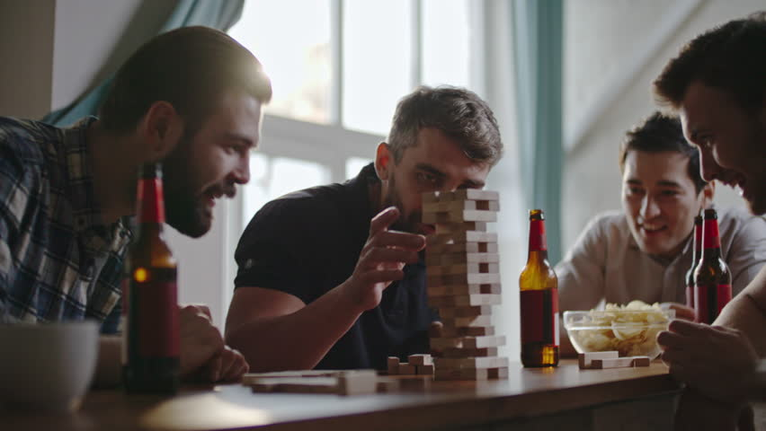 Guys laughing and high-fiving each other as their friend making jenga tower fall by accident #21345202