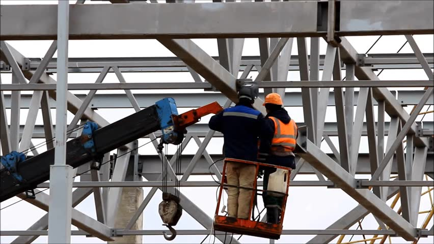A welder working at height without insurance in a cradle lift in the construction of large shopping complex metal structures and concrete piles | Shutterstock HD Video #21353782