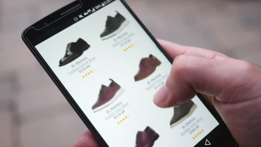 MONTREAL, CANADA - November 2016 : Shopping shoes online on mobile website on a smartphone.