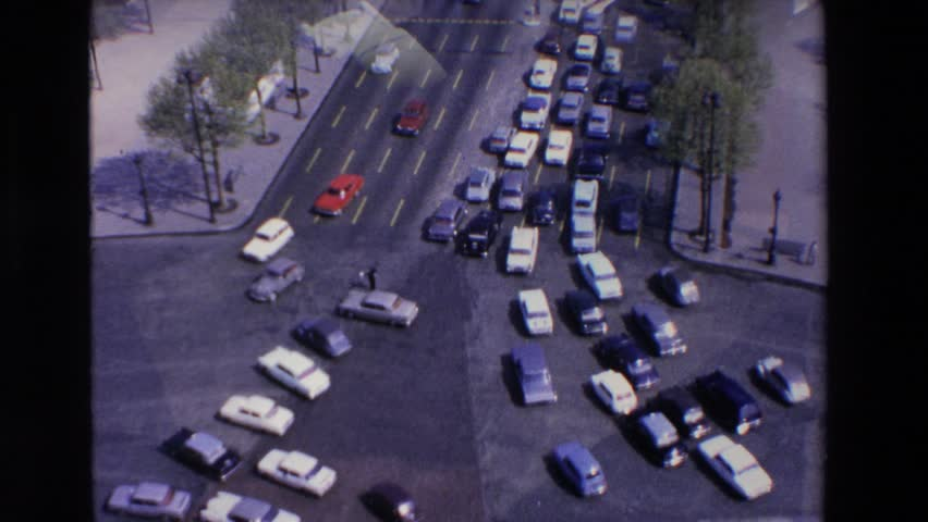 LOURDES, FRANCE 1969: a multitude of cars drive to and fro in a town as a traffic jam begins on one street. #21361393
