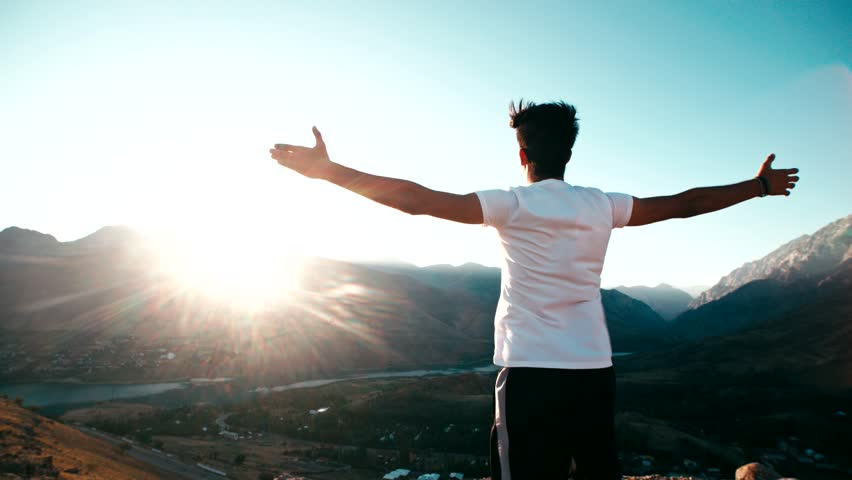 young Asian male reaching to the top of the mountain area, standing on top of a mountain, hands raised, awareness of success, slow motion #21388735