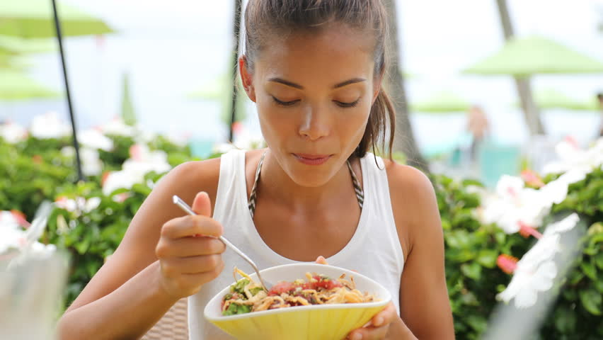Woman eating salad at restaurant outdoors in summer. 59.94 FPS.