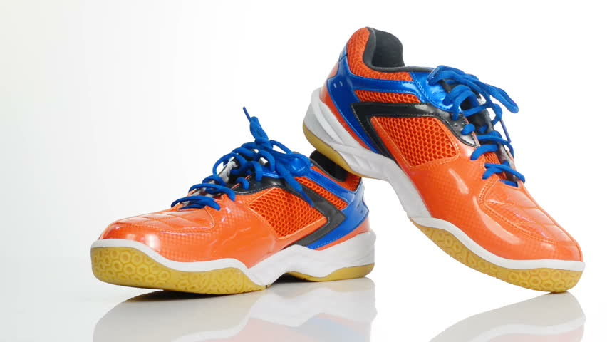 Orange sport badminton shoes rotating over white background