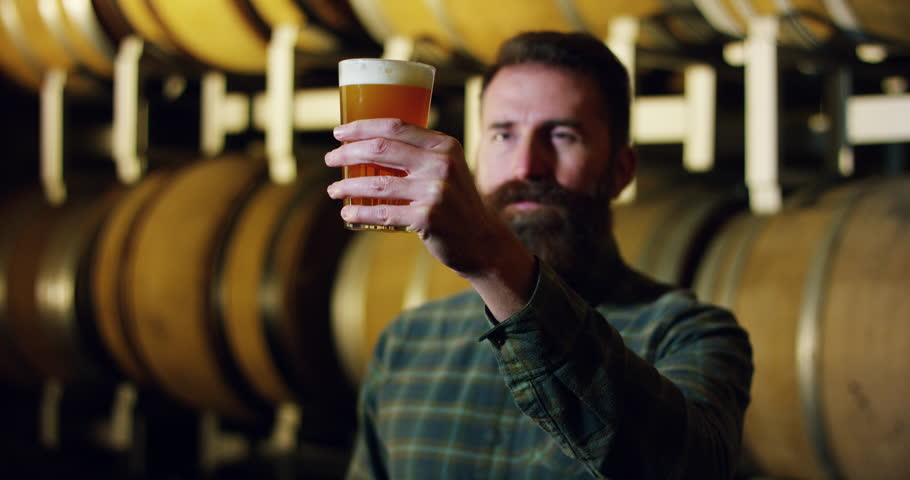 A brewmaster expert checks the quality of the freshly tapped beer from wooden barrels formerly used for flavour the wine or beer. passion for beer and wine. old and traditional jobs. | Shutterstock HD Video #21399301