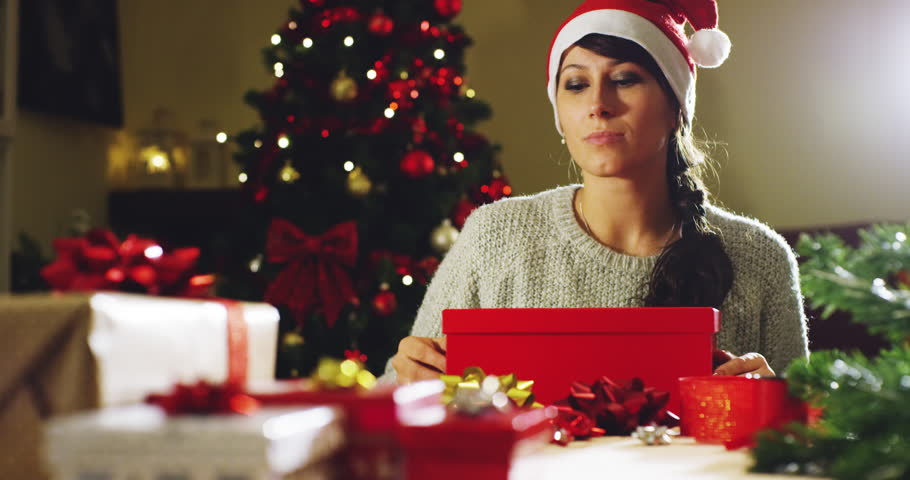 Girl with Christmas hat makes wishes and opens a Christmas gift package. concept of holidays and new year. the girl is happy and smiles with christmas gift in hand. | Shutterstock HD Video #21399454