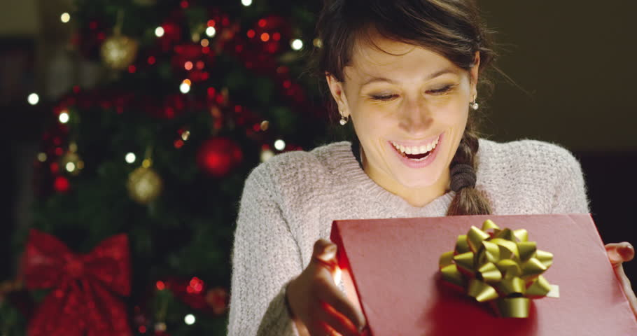 Girl with Christmas hat makes wishes and opens a Christmas gift package. concept of holidays and new year. the girl is happy and smiles with christmas gift in hand.