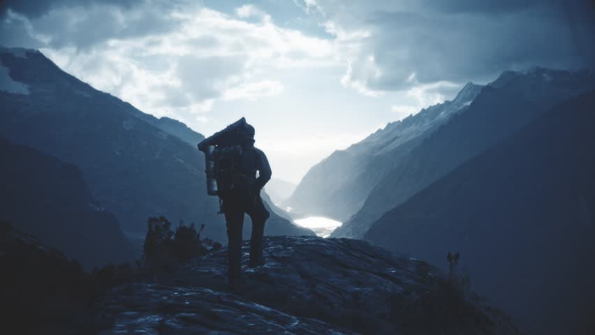 Silhouette of backpacker walking towards the edge of a rocky peak to contemplate the beautiful panorama of the Huascaran National Park. Slow motion Royalty-Free Stock Footage #21402010