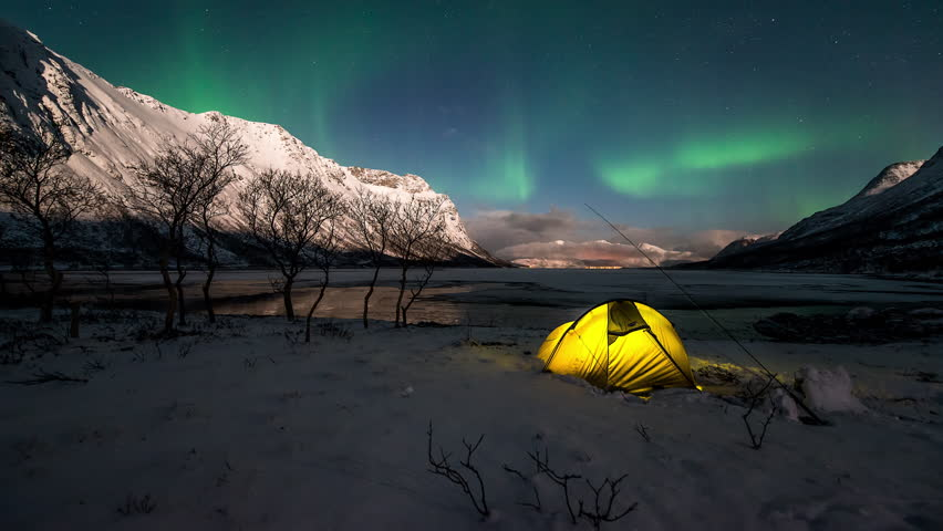 Northern Lights over an illuminated tent in a norwegian fjord in winter.