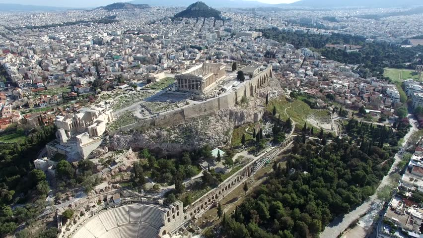 Aerial drone bird-eye view moving around back of the Acropolis of Athens ancient citadel located on rocky outcrop showing Parthenon very famous tourist attraction in Europe Greece European visit 4k