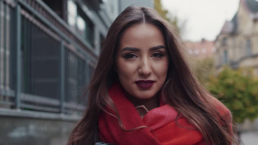 Attractive smiling girl in a vivid red scarf, with long hair and perfect makeup. Amazing young woman happily wonders in the autumn city. Freedom. Urban style. Stylish look. Happy moments. #21456640