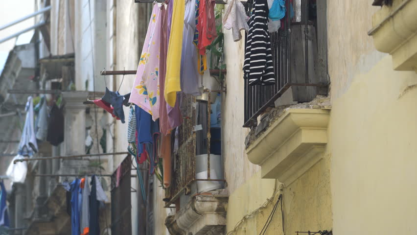 HAVANA, CUBA - SEPTEMBER 17, 2016: View to old balcony on a colonial Havana street where the multi-colored wet clean washed clothes of local people are drying at summer sunny day | Shutterstock HD Video #21463177