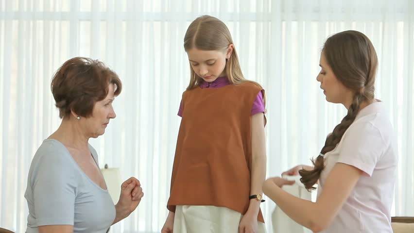Girl trying on a dress with a top and a silk belt, two women helping her