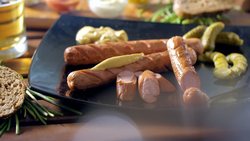 Eating a tasty bratwurst dressed with mustard with a fork during a breakfast. Warm and tasty mood. Very closeup shot